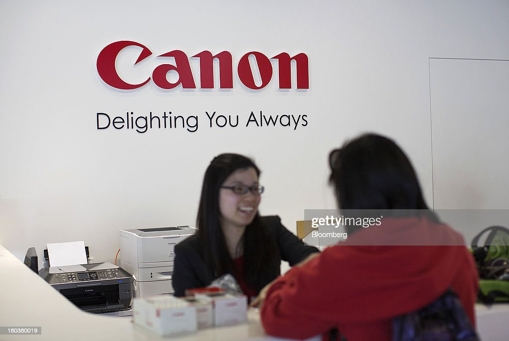 A Canon Inc. employee, left, attends to a customer at the company's showroom in Hong Kong, China, on Tuesday, Jan. 29, 2013. Canon, the world's largest camera maker, forecast profit will rise 14 percent this year amid a weaker yen and the withering of a boycott of Japanese goods in China. Photographer: Jerome Favre/Bloomberg via Getty Images