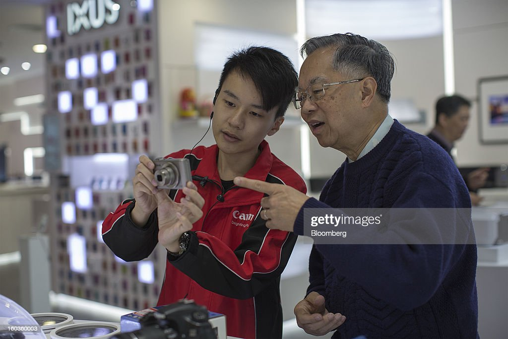 A Canon Inc. employee, left, demonstrates the PowerShot S110 digital compact camera to a customer at the company's showroom in Hong Kong, China, on Tuesday, Jan. 29, 2013. Canon, the world's largest camera maker, forecast profit will rise 14 percent this year amid a weaker yen and the withering of a boycott of Japanese goods in China. Photographer: Jerome Favre/Bloomberg via Getty Images