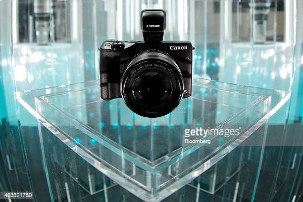 A Canon Inc EOS M3 mirrorless digital camera sits on display in this photograph taken with a fisheye lens at the CP Camera and Photo Imaging Show in...