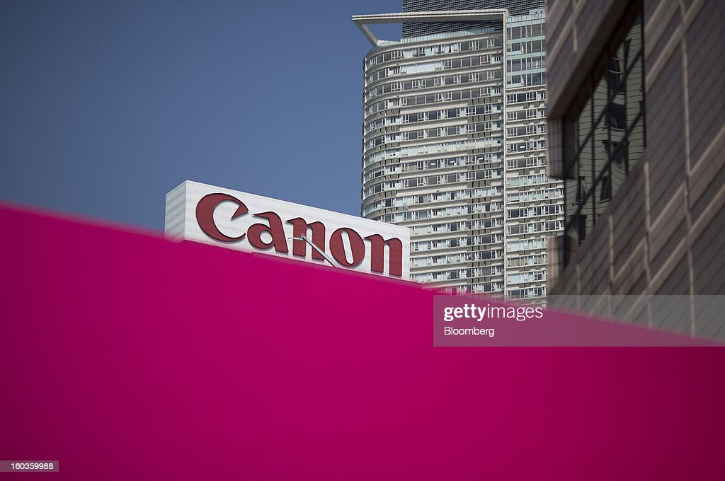 Canon Inc. signage is displayed on top of a building behind a barrier in Hong Kong, China, on Tuesday, Jan. 29, 2013. Canon, the world's largest camera maker, forecast profit will rise 14 percent this year amid a weaker yen and the withering of a boycott of Japanese goods in China. Photographer: Jerome Favre/Bloomberg via Getty Images