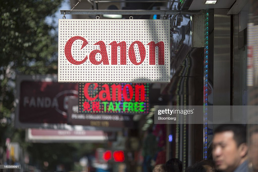 Canon Inc. signage is displayed outside electronics stores on Nathan Road in Hong Kong, China, on Tuesday, Jan. 29, 2013. Canon, the world's largest camera maker, forecast profit will rise 14 percent this year amid a weaker yen and the withering of a boycott of Japanese goods in China. Photographer: Jerome Favre/Bloomberg via Getty Images