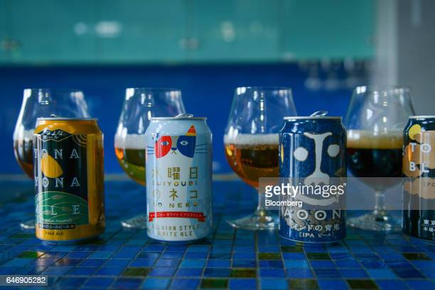 Cans and snifters of YoHo Brewing Co brand Yona Yona Ale from left Suiyobi No Neko Indo No Aooni and Tokyo Black beer sit on display at the company's...