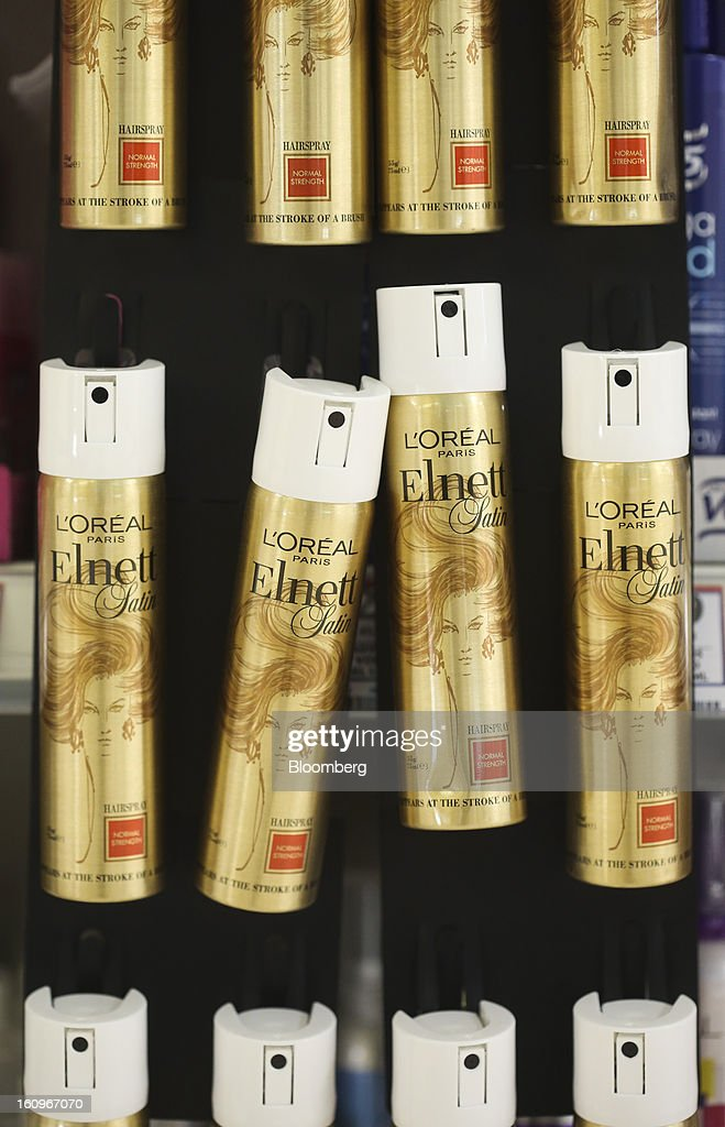 Cans of Elnett hair spray, produced by L'Oreal SA, hang on a display inside a supermarket in London, U.K., on Friday, Feb. 8, 2013. Britain's economy will grow more slowly this year than previously forecast and stagnation may persist, according to the National Institute of Economic and Social Research. Photographer: Chris Ratcliffe/Bloomberg via Getty Images