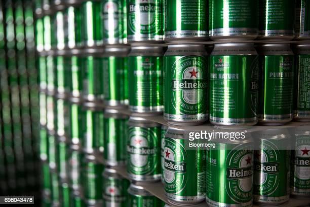 Cans of Heineken beer sit stacked in the bottling plant at the Heineken NV brewery in Yangon Myanmar on June 15 2017 Heineken is seeking to exploit...