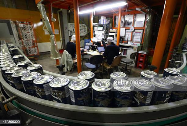 Cans of Indo no Aooni craft beer move along a conveyor as employees use laptop computers on the production line of the YoHo Brewing Co brewery in...
