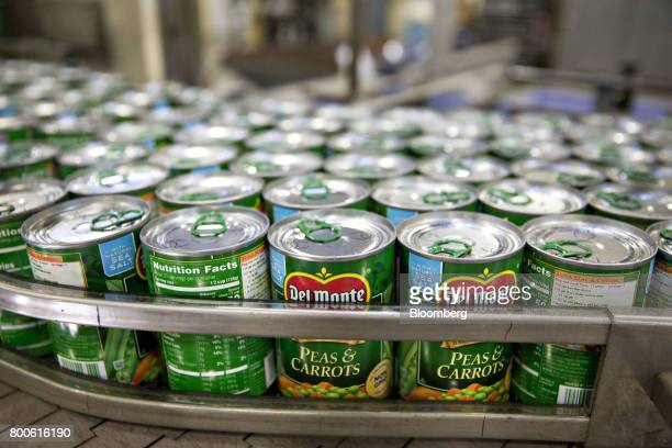 Cans of peas and carrots move along a conveyor belt after being labeled at the Del Monte Foods Inc facility in Mendota Illinois US on Friday June 23...