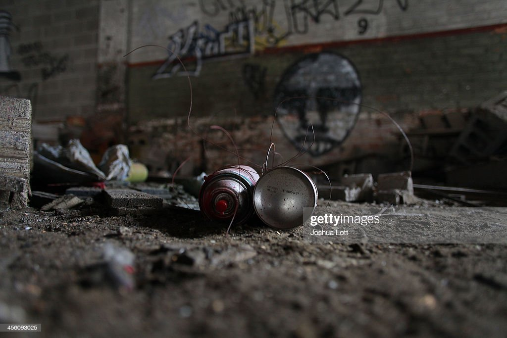 Cans of spray paint sit near graffiti on the walls of the abandoned Packard Automotive Plant December 13, 2013 in Detroit, Michigan. Peru-based developer Fernando Palazuelo made his final payment on the Packard Plant, which he won during a Wayne County auction for $405,000. Palazuelo plans on developing the former automotive plant where luxury Packard cars were made in the coming years.