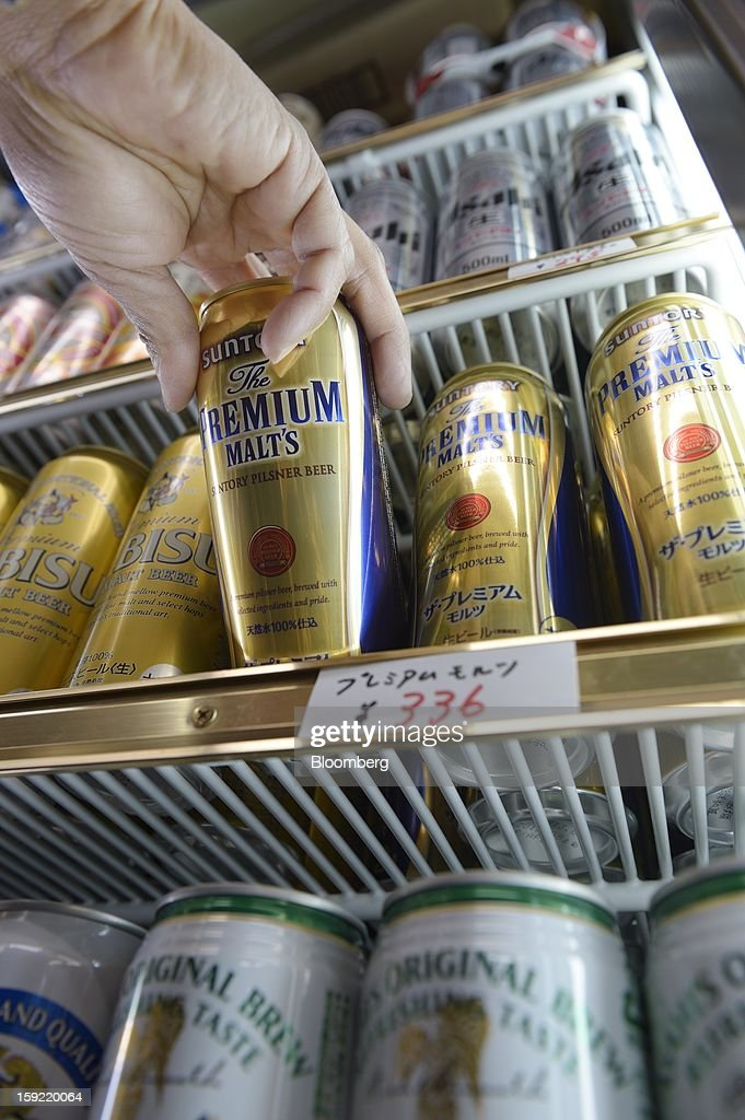 Cans of Suntory Holdings Ltd. Premium Malt's beer are displayed for sale in a liquor store in Kawasaki, Kanagawa Prefecture, Japan, on Wednesday, Jan. 9, 2013. Suntory Holdings Ltd. plans to hire Nomura Holdings Inc. as a lead underwriter for the initial public offering of its non-alcoholic drinks and food business, said two people with direct knowledge of the matter. Photographer: Akio Kon/Bloomberg via Getty Images