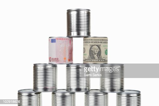 Cans pyramid surrounded by US dollar and Euro note : Stock Photo