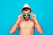 I can't believe my eyes! Astonished, surprised, attractive man with naked torso over blue background looking out glasses on his face, holding eyelets with hands, having wide open mouth