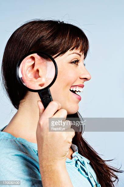 I can't hear you! Magnifying glass enlarges smiling woman's ear