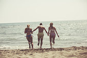 Rear view of three young people holding hands and running toward sea.