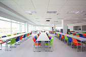 Canteen interior with white table and blue, green, orange chairs.