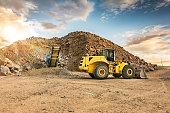 Cantera al aire libre con maquinaria pesada, silos y cinta mecanica para transporte de piedra