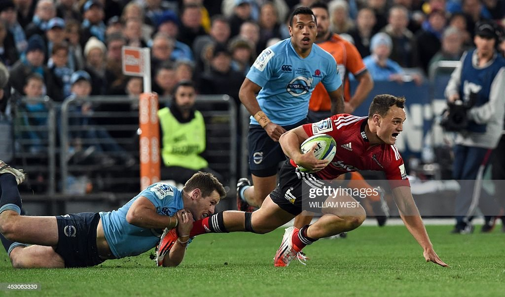 Canterbury Crusaders fullback Israel Dagg (R) is tackled by New South Wales Waratahs flyhalf Bernard Foley (L) in the Super 15 rugby union final in Sydney on August 2, 2014. AFP PHOTO/William WEST --IMAGE