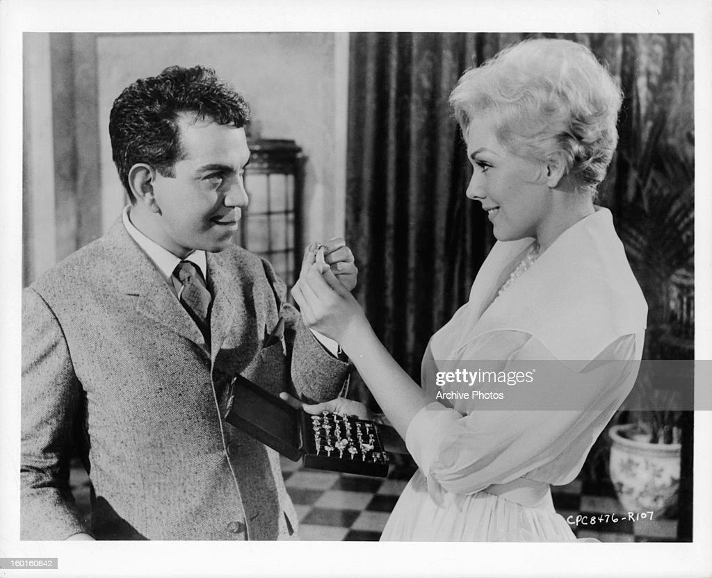 Cantinflas and Kim Novak exchanging item in a scene from the film 'Pepe', 1960.