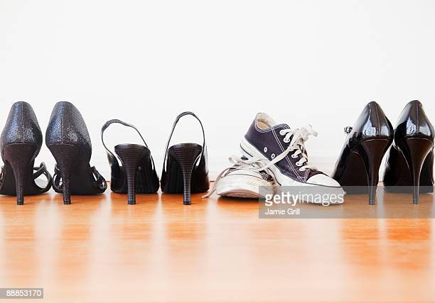 Canvas shoe in row of elegant high heel shoes