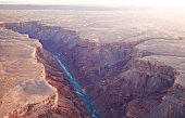 Aerial Image of a canyon with a river flowing through it with cliffs on a warm sunny day in the evening