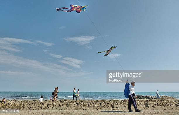 Caorle Veneto Italy May 2014 Early spring seazon at the Adriatic Sea beach in Caorle resort Kites seller an immigrant from Africa walks on the beach
