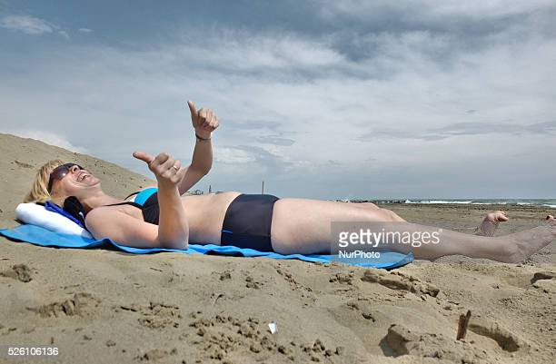 Caorle Veneto Italy May 2014 Early spring seazon at the Adriatic Sea beach in Caorle resort Young lady lays on the sandy beach and sunbathing