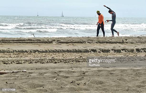 Caorle Veneto Italy May 2014 Early spring seazon at the Adriatic Sea beach in Caorle resort Two mans swimers goes on the sandy beach in front of sea...