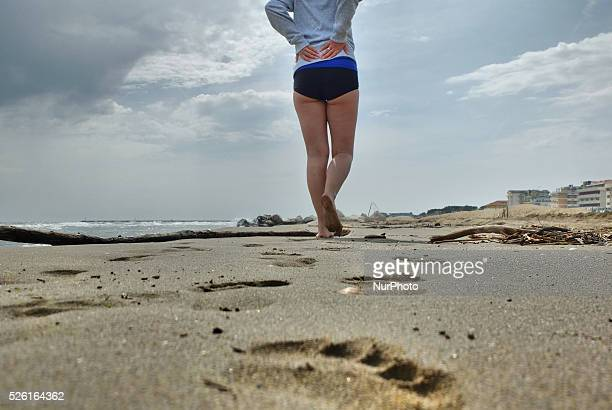 Caorle Veneto Italy May 2014 Early spring seazon at the Adriatic Sea beach in Caorle resort Young woman walks on the beach visible footprints
