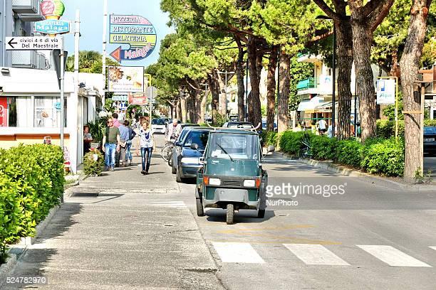 Caorle Veneto Italy May 2014 Eldery couple walks on the street in the Caorle resort at the Adriatic sea Italian motorbike van stands on the street...