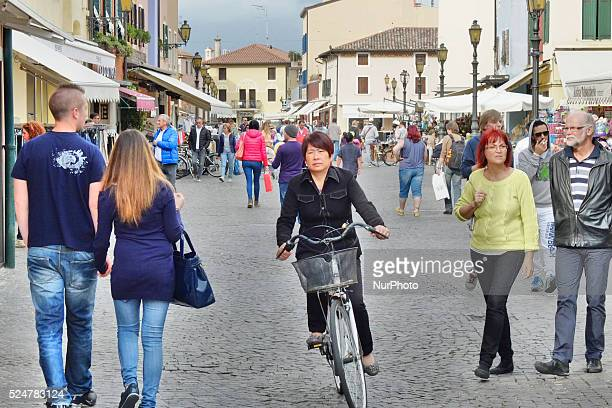 Caorle Veneto Italy May 2014 Lady rides on the bicycle along the old market street in the Caorle Italy