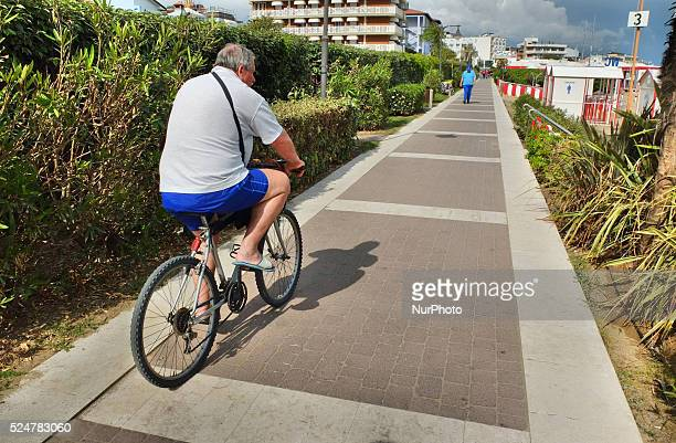 Caorle Veneto Italy May 2014 Man rides on the bike along the promenade at the Adriatic sea coast in the Caorle resort