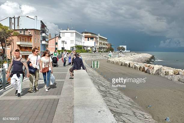 Caorle Veneto Italy May 2014 People walks along the promenade at the Adriatic sea coast in the Caorle resort