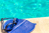 cap and goggles on the edge of the pool
