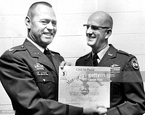 Cap Commander Honored Col Arthur F Putz left Colorado wing commander of the Civil Air Patrol is shown receiving a 'ManofAction' citation from Lt Col...