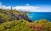 Panoramic view of scenic coastal landscape with traditional lighthouse at famous Cap Frehel peninsula, Bretagne, northern France.