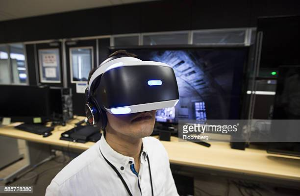 A Capcom Co employee wearing a Sony Computer Entertainment Inc PlayStation VR headset demonstrates the Resident Evil 7 Biohazard VR game at the...