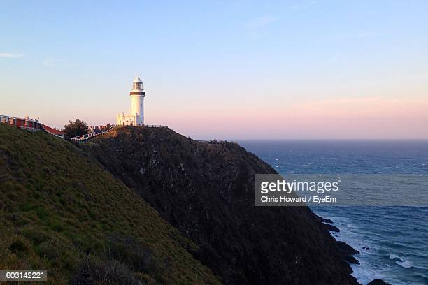 Cape Byron Light On Mountain By Sea Against Sky During Sunset