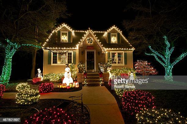 A Cape Cod style house in Medford NJ is outlined with White Christmas lights with colored lighted brushes and trees