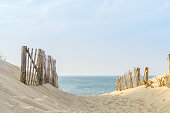 two fences frame the pathway to the beach at Provincetown Massachusetts, at sunset
