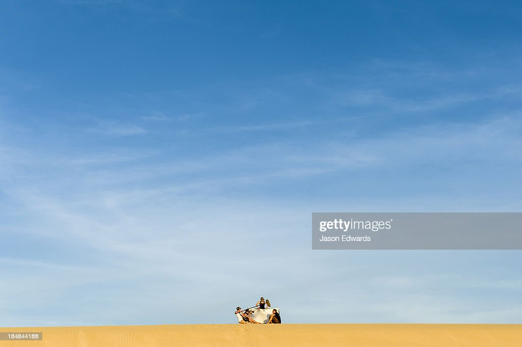 A film crew records an interview on a coastal sand dune at sunset.