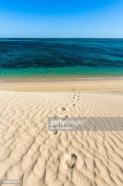 A lone swimmer hikes down a sand dune into turquoise seas to cool off.