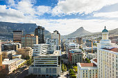 Downtown Cape Town, business district with skyscrapers and highrise buildings, underneath famous Table Mountain at the left and Lion's Head at the right.