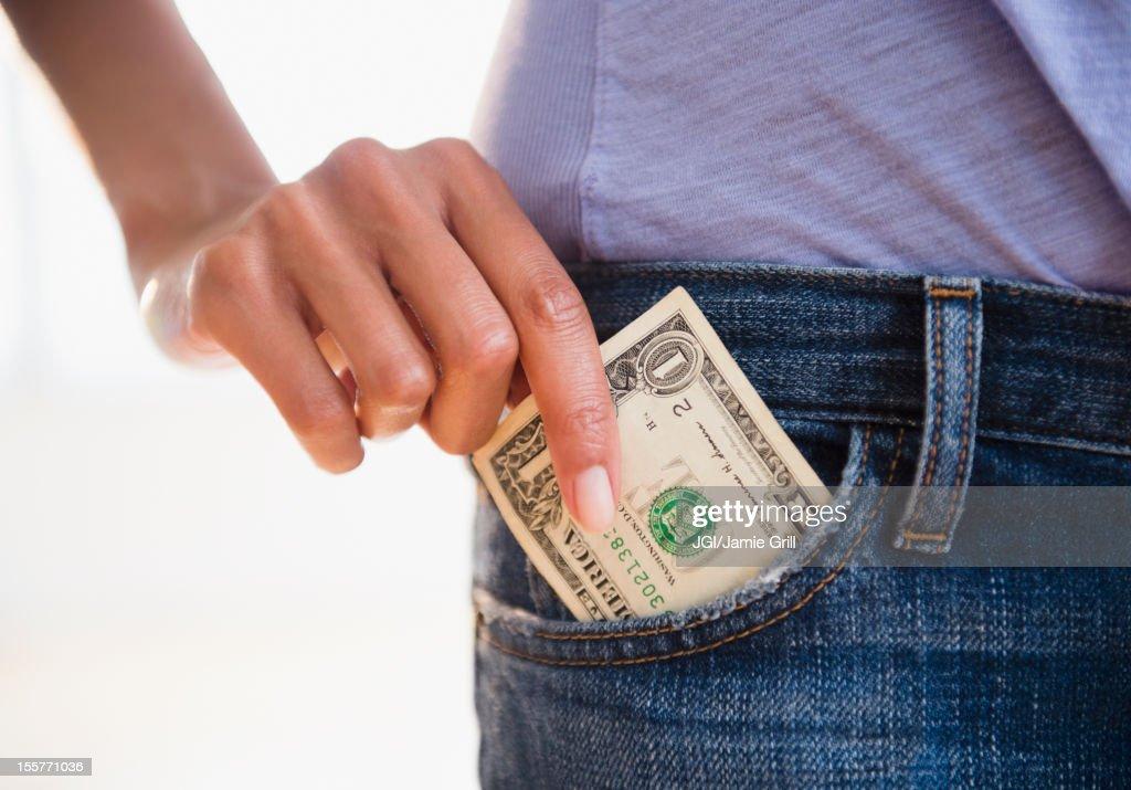 Cape Verdean woman taking dollar bill from pocket