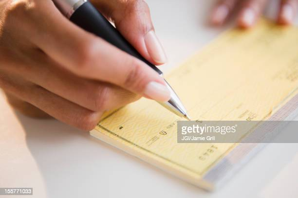 Cape Verdean woman writing a check