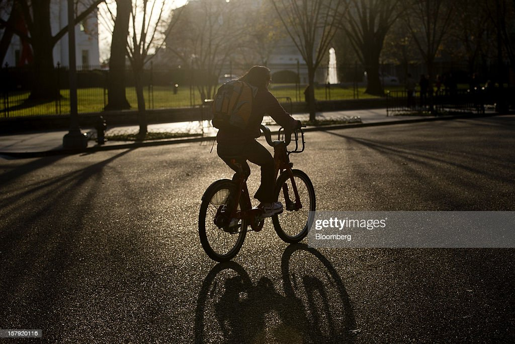 A Capital Bikeshare bicyclist rides past the White House in Washington, D.C., U.S., on Friday, Nov. 30, 2012. Since Sept. 2010, Capital Bikeshare has dispersed more than 1700 bikes for rent across the city and has totaled over 3.5 million rides since Sept. 2011. Alta Bicycle Share, the company that was awarded the contract to run the program, has installed 191 solar-powered docking stations throughout the District and Arlington, Virginia. Photographer: Andrew Harrer/Bloomberg via Getty Images