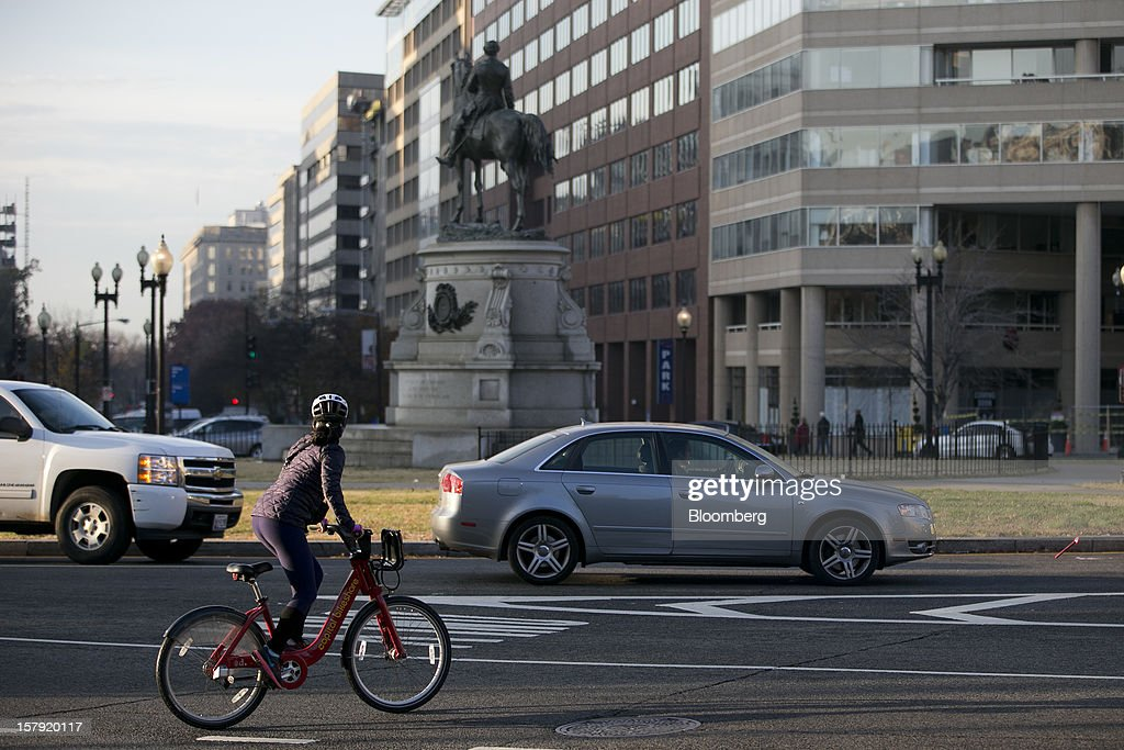 A Capital Bikeshare bicyclist rides through Thomas Circle in Washington, D.C., U.S., on Monday, Dec. 3, 2012. Since Sept. 2010, Capital Bikeshare has dispersed more than 1700 bikes for rent across the city and has totaled over 3.5 million rides since Sept. 2011. Alta Bicycle Share, the company that was awarded the contract to run the program, has installed 191 solar-powered docking stations throughout the District and Arlington, Virginia. Photographer: Andrew Harrer/Bloomberg via Getty Images