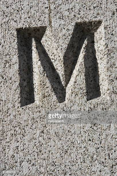 Capital letter M engraved in stone