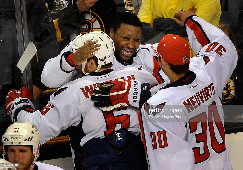 Capitals Joel Ward (42), center, is embraced by teammate Dennis Wideman (6), left, after scoring the game winning goal as the Washington Capitals defeat the Boston Bruins 2 -1 in overtime in game 7 of the first round of the NHL playoffs at the TD Garden in Boston MA. April 25, 2012