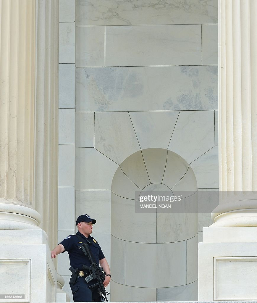 A Capitol Hill Police officer is seen on the steps of the US Capitol on April 17, 2013 in Washington, DC after the Hart Senate Office Building nearby was closed. US Capitol Police are investigating several suspicious packages that were delivered to the Hart and Russell Senate Office buildings. AFP PHOTO/Mandel NGAN