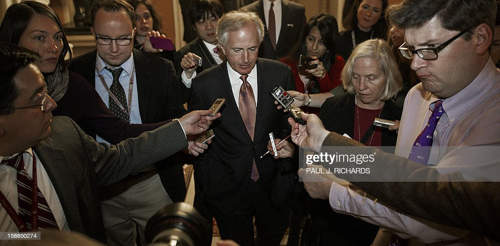 Capitol Hill reporters follow US Senator Bob Corker (C) after he attended a Rebublican Caucus on the progress on the impending fiscal cliff at Capitol Hill in Washington late on December 31, 2012. Coming together in the early hours of 2013, the US Senate overwhelmingly passed a last-gasp bill on January 1, 2013 to avert huge tax increases and draconian spending cuts making up the so-called 'fiscal cliff.' AFP PHOTO/Paul J. Richards