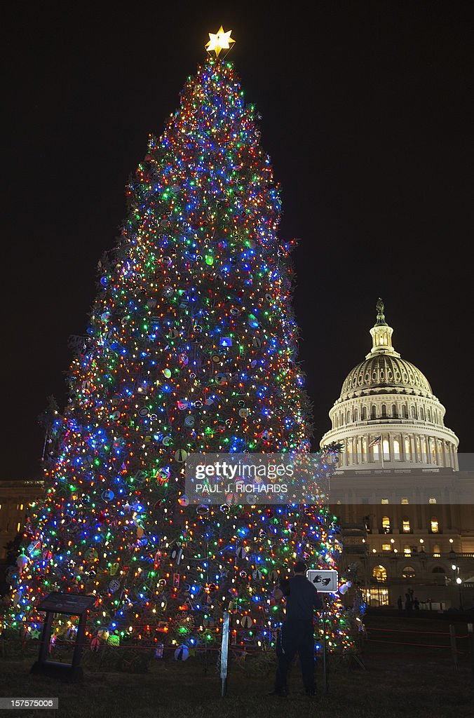 A Capitol Hill workman rolls up a microphone cord after the US Capitol Christmas Tree lighting ceremony on December 4, 2012 on the West Front Lawn of the US Capitol in Washington. AFP PHOTO/Paul J. Richards