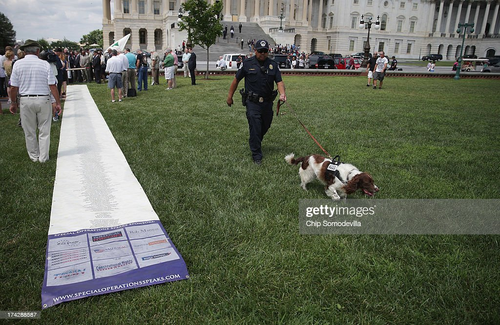S. Capitol Police K9 and officer walk past the Special Operations Speaks (SOS) Political Action Committee's 60-foot-long petition demanding a House Select Committee investigate the Benghazi terrorist attck outside the U.S. Capitol July 23, 2013 in Washington, DC. The scroll bears the names of more than 1,000 Special Service veterans who support a full investigation of the September 11, 2012, Benghazi attacks.